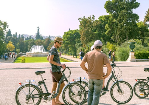 some cyclists visit the national gardens and stop in front of one of the fountains