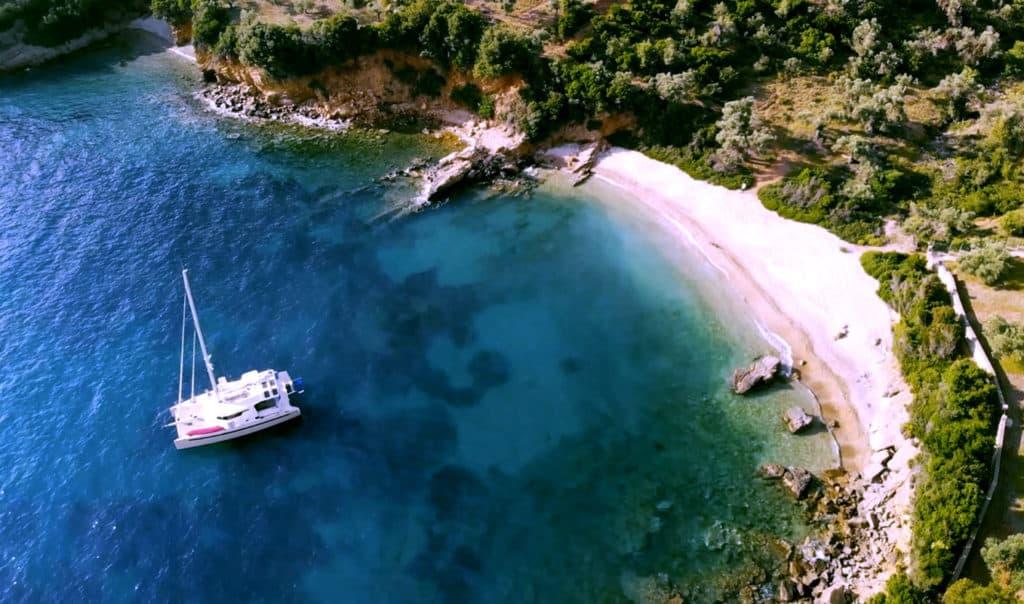 a catamaran floats near a beautiful sandy beach. Sporades Yacht holidays