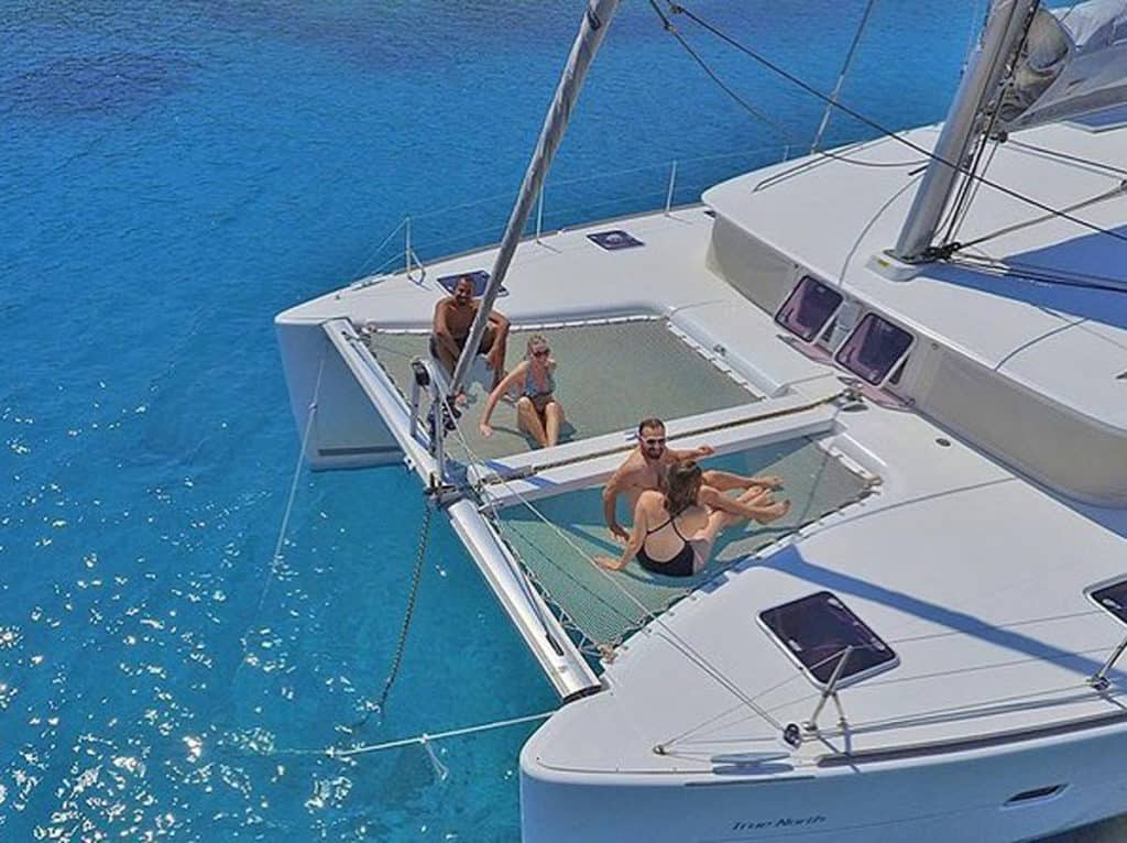 catamaran with couples enjoying the sun. Cyclades Yacht holidays