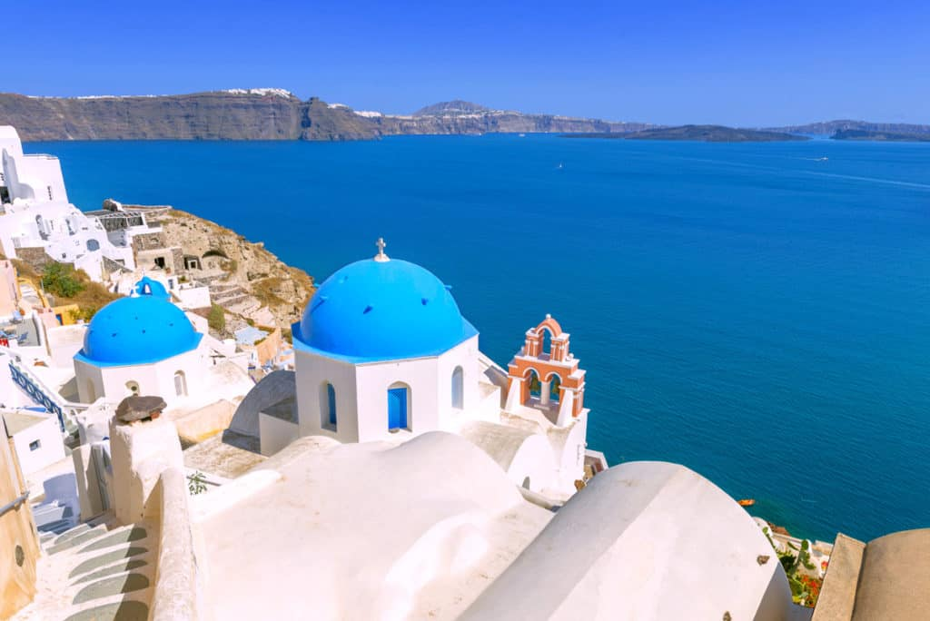 blue domed churches of santorini overlooking the Aegean sea in the Cyclades visited on our cyclades sailing holidays