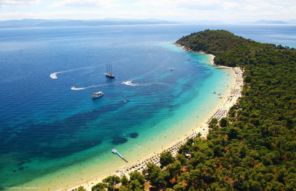 beautiful sandy beach on Skiathos Island with sailing yachts anchored in the bay. Sporades yacht charter