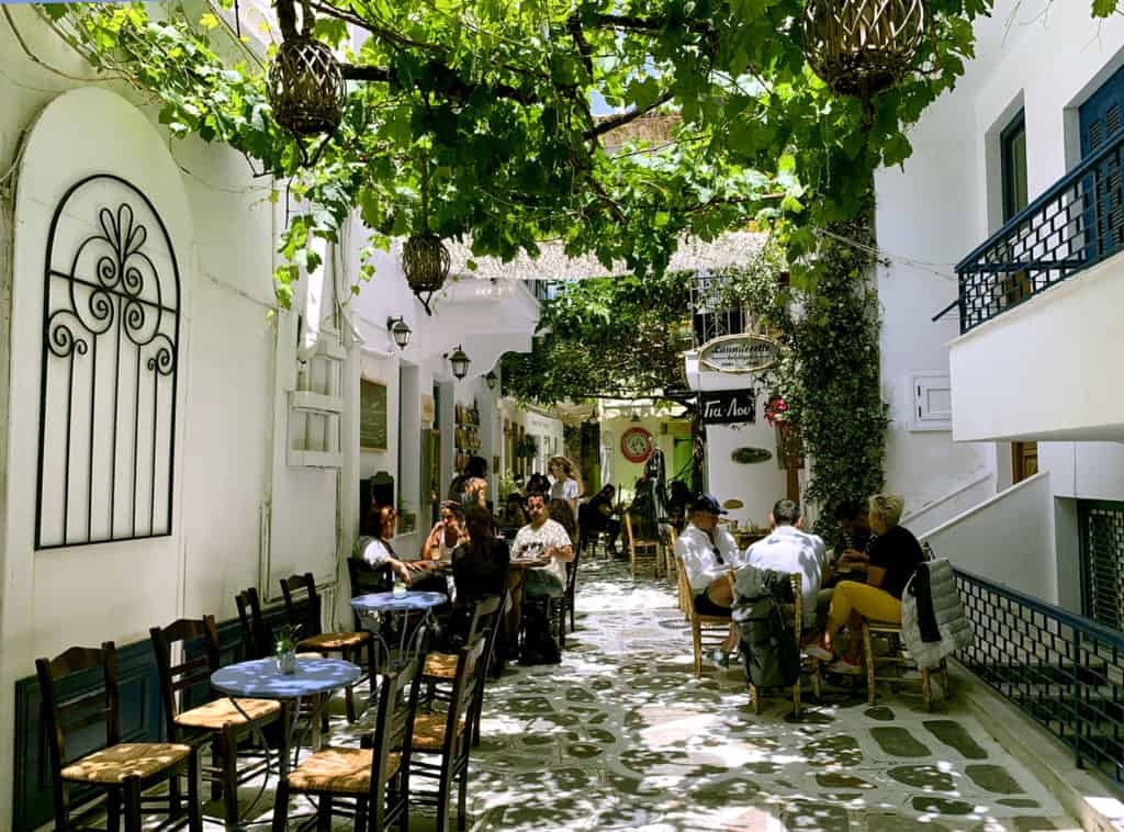 tourist enjoy the pretty streets of Tinos town. Cyclades skippered sailing holidays