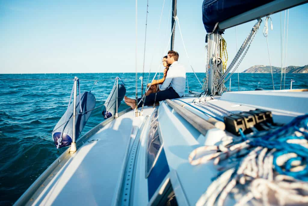 a man and woman together on the deck of a sailing yacht in the ionian islands