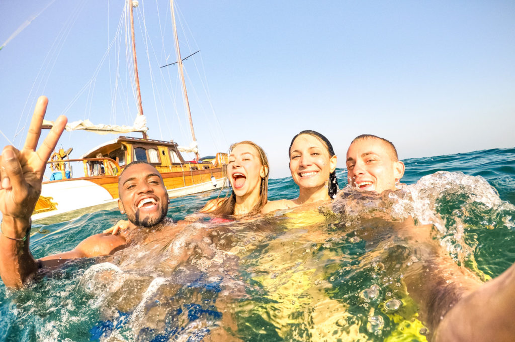 friends on vacation in the ionian islands of Greece swim in the sea together taking a photo