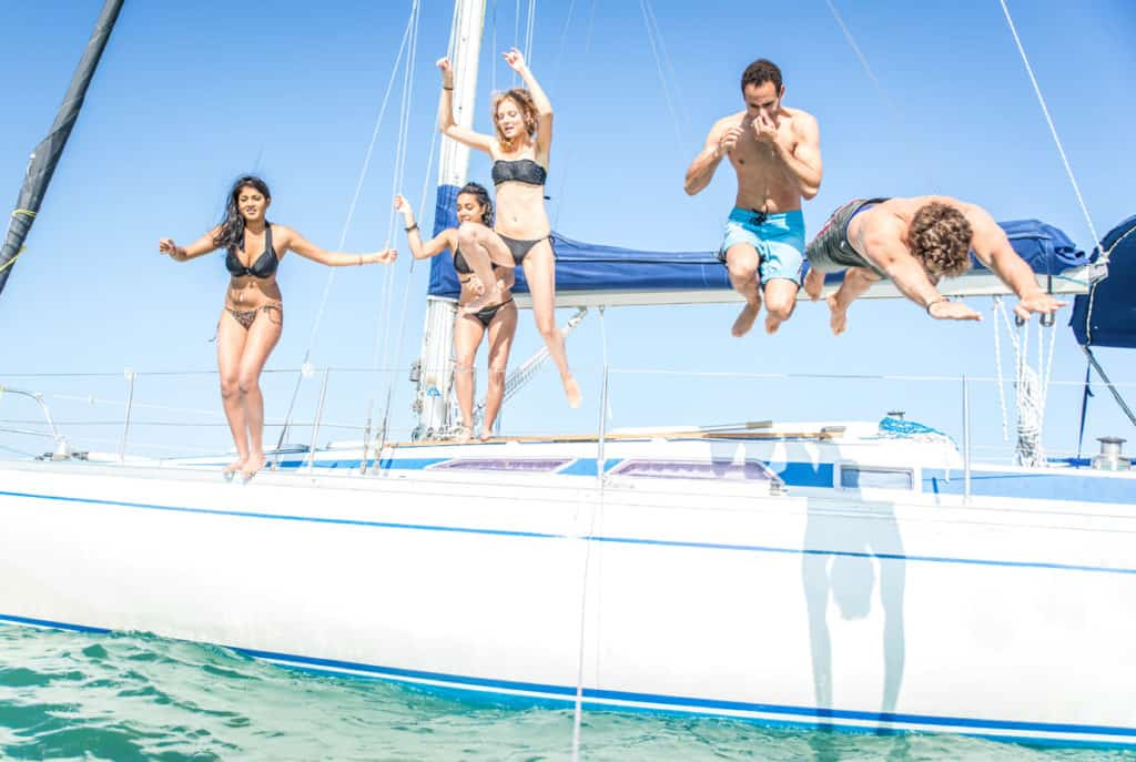 a family jump from the deck of a sail yacht into the sea in the ionian islands
