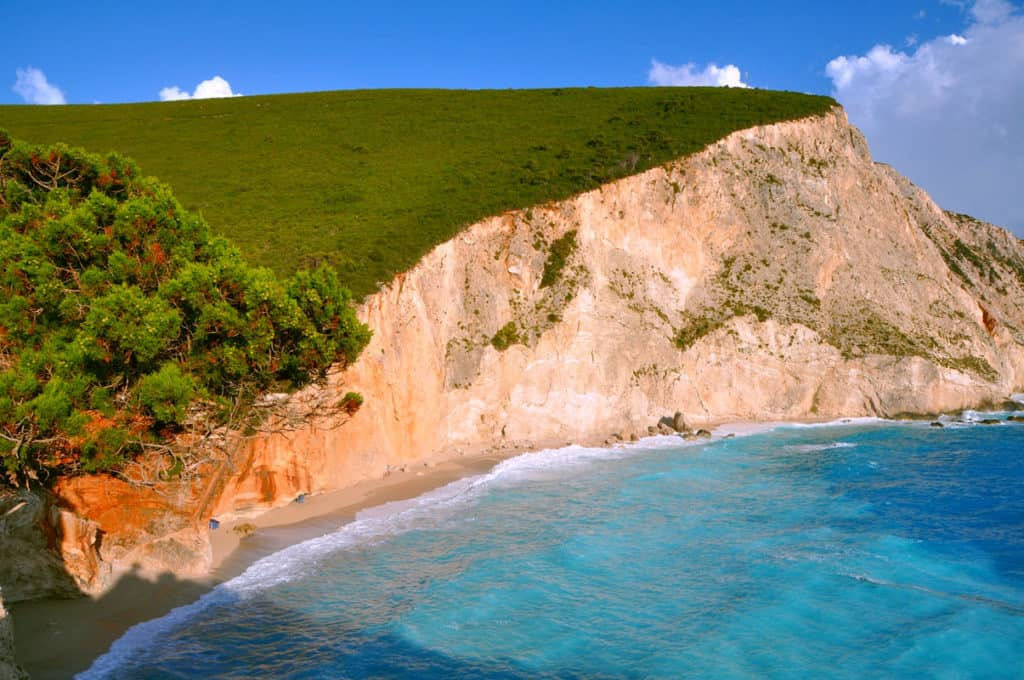 a tall cliff of an ionian island with the deep blue sea beneath