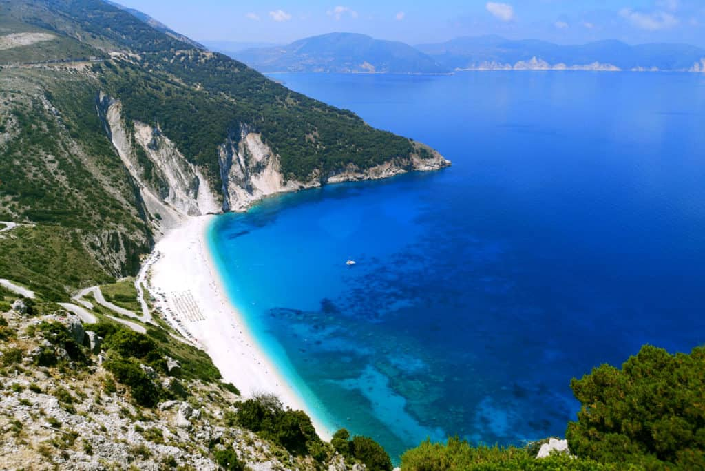 panoramic view of a beautiful sandy beach in the ionian islands with a skippered sailing yacht sitting on the blue sea