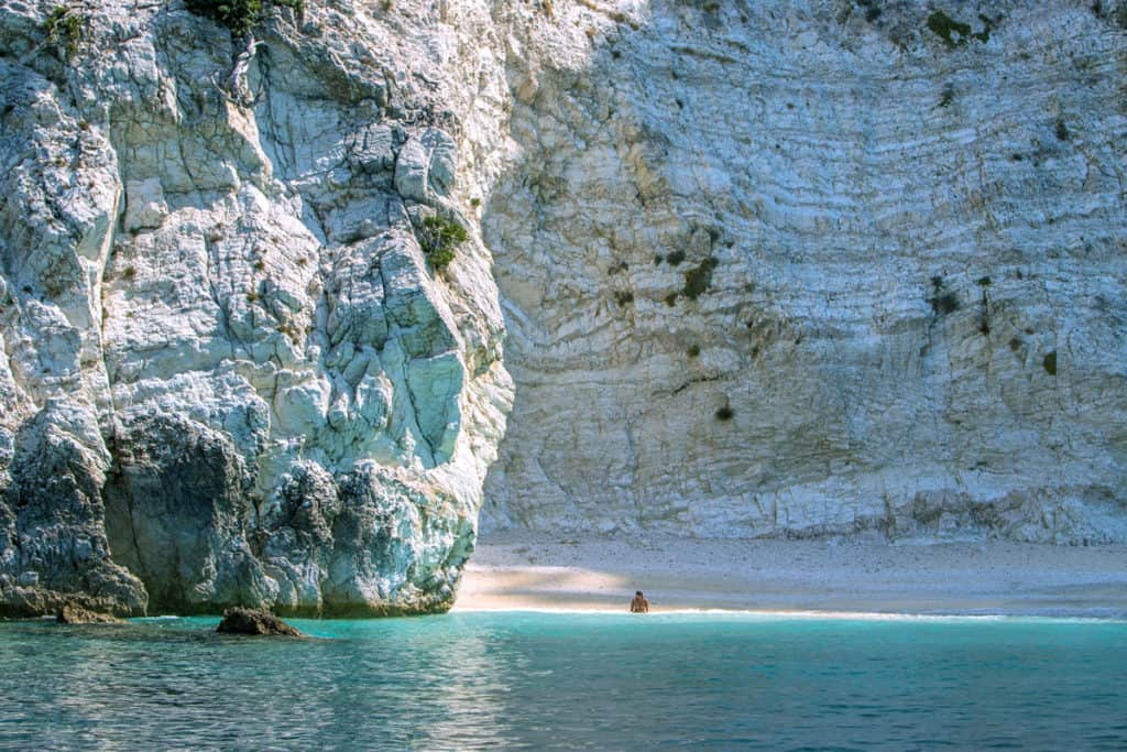 a tourist swims in the clear blue water of the ionian sea beneath a white cliff