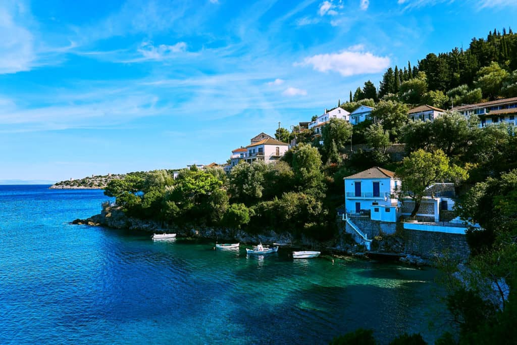 a small bay in the ionian islands with a village above the blue water