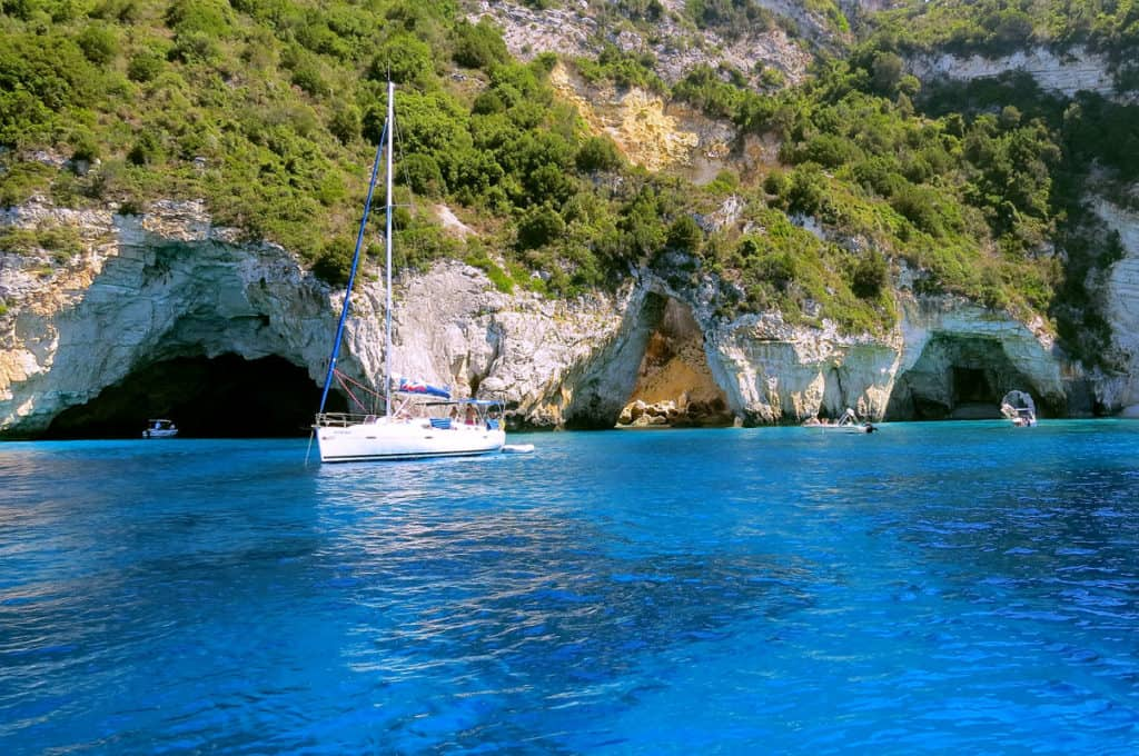 a skippered sailing yacht visits caves along the shore of the ionian islands as the tourists take a small boat into the caves