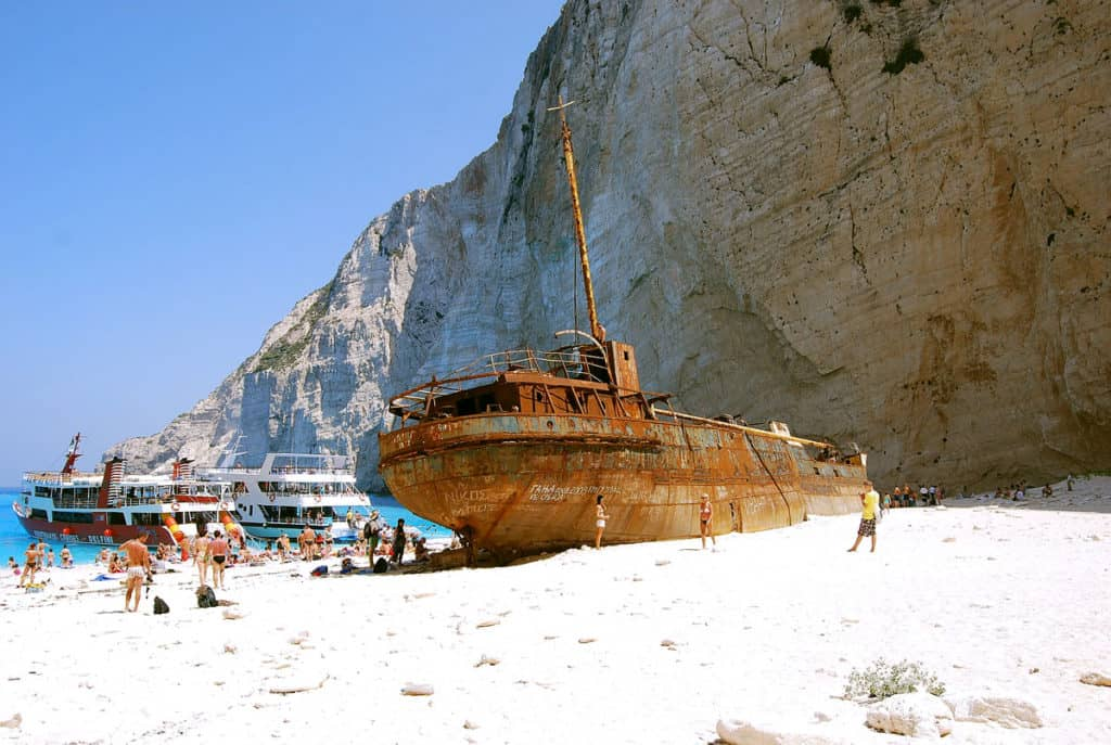 a shipwreck lies on the white sandy beach of an ionian island visited by a boat of tourists
