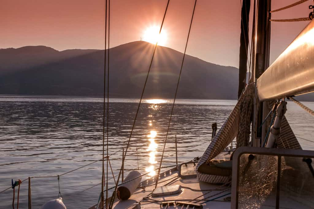 a skippered sailing yacht sails at sunset in the Ionian sea in Greece