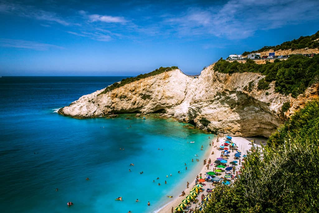 steep white cliffs of an ionian island plunge down to a white sandy beach with sunbathers