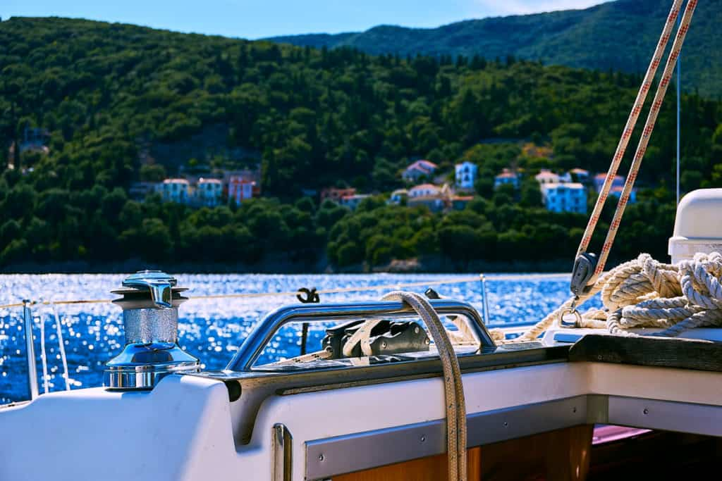 view to the shore of an ionian island from the deck of a luxury skippered sailing yacht