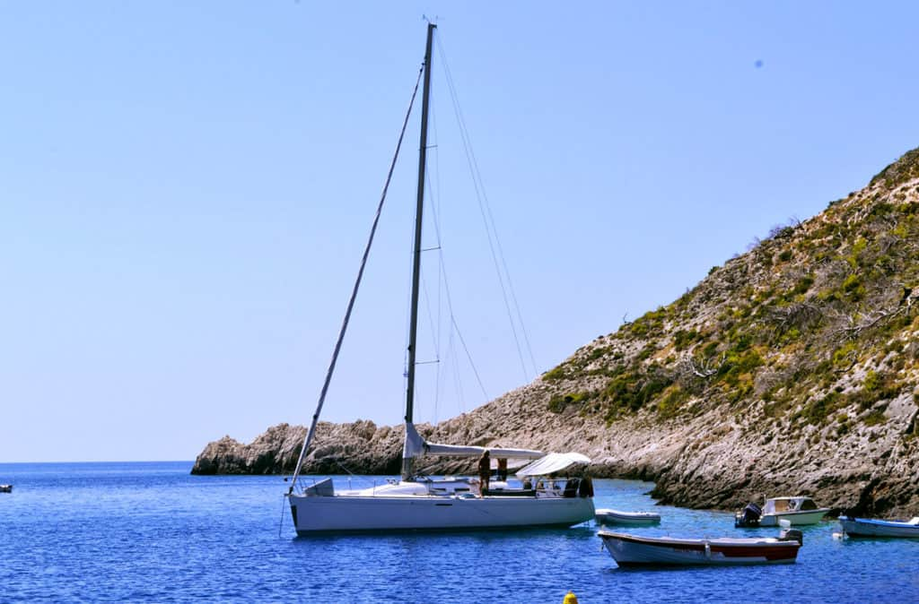 a skippered sailing yacht sits on the ionian sea with a rocky islet in the background