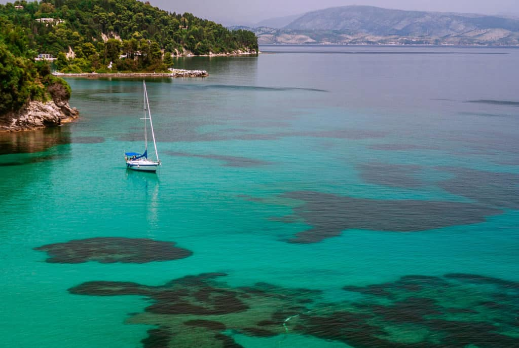 a crewed sailing yacht sails off the shore of an ionian island with green trees above the rocky shoreline