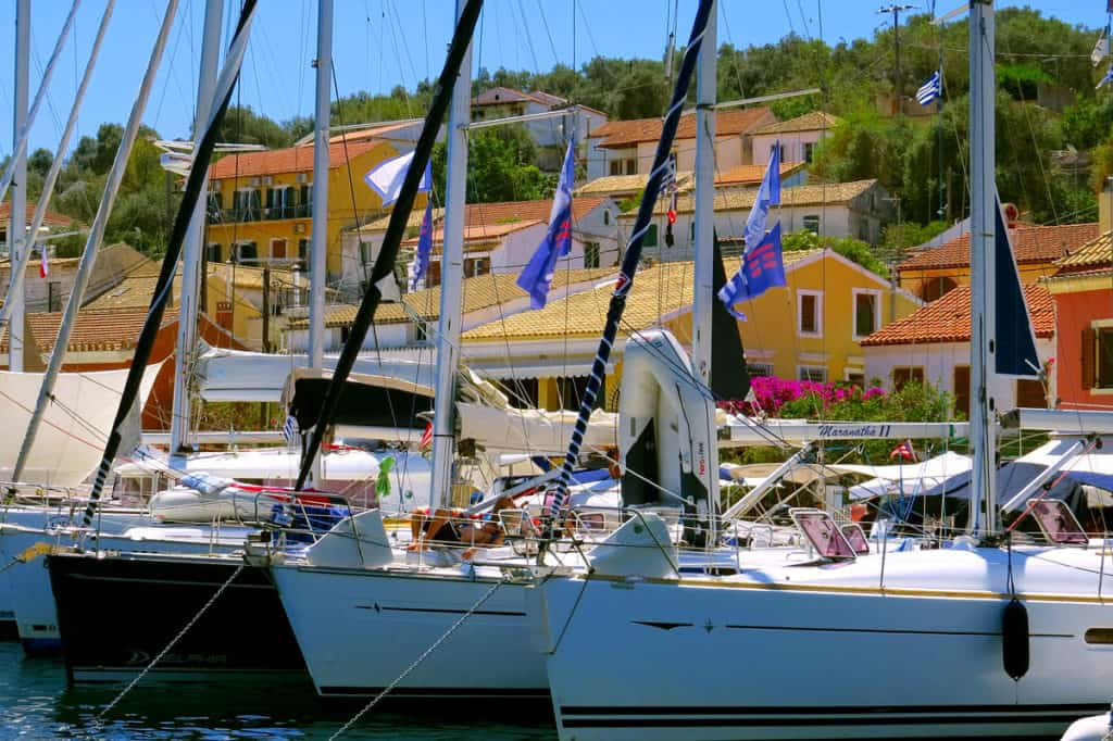 a line of sailing yachts wait at a pretty port in the Ionian Islands with neoclassical houses in the background