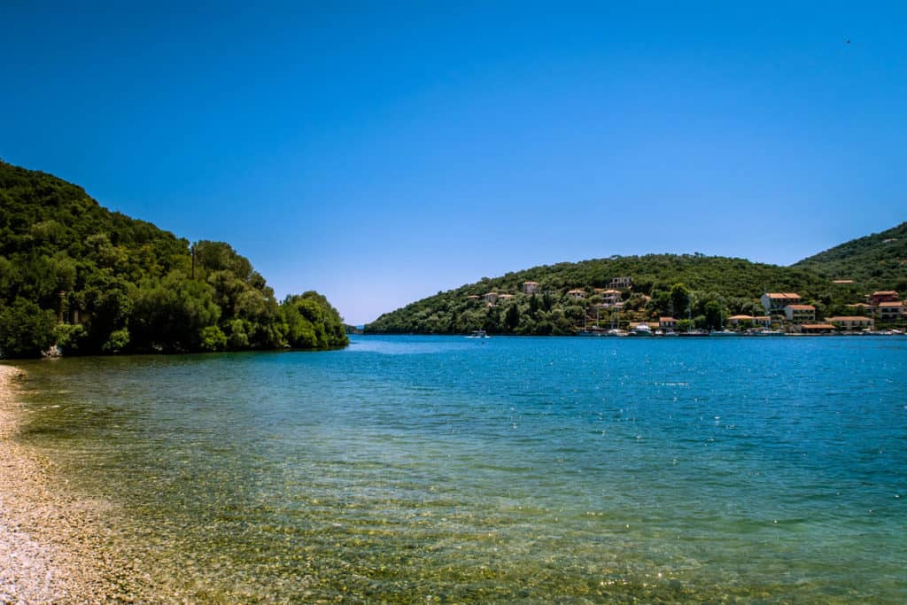 a desearted pebbled beach with clear blue water in the ionian islands