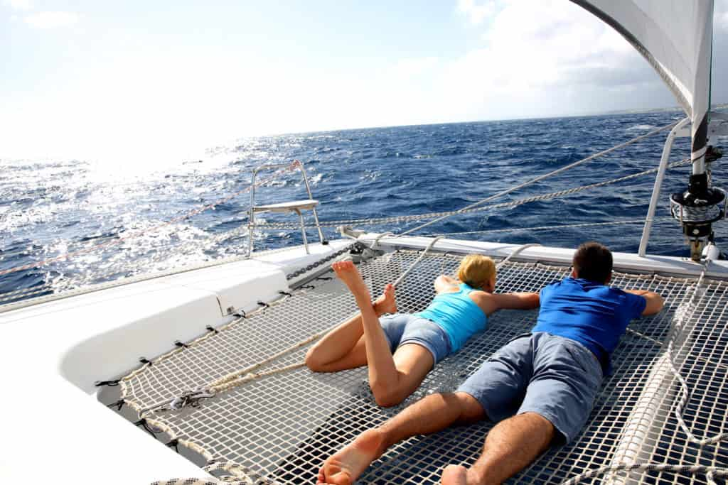 two tourists relax on a catamaran during a skippered sailing greece holiday