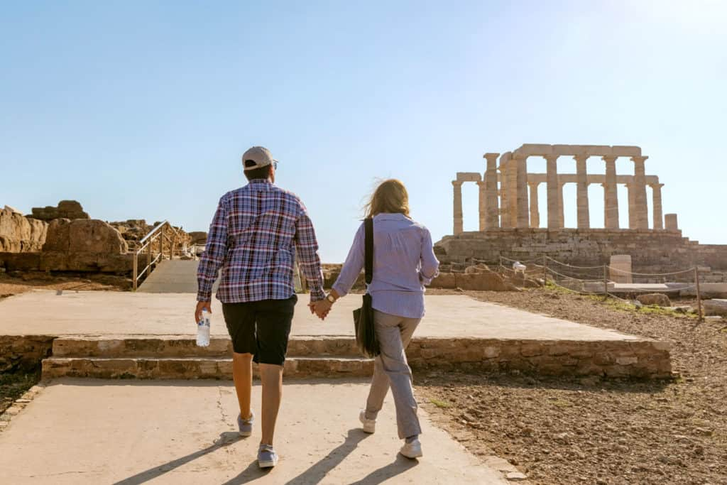 a couple go up to the ancient greek temple of Poseidon skippered sailing greece