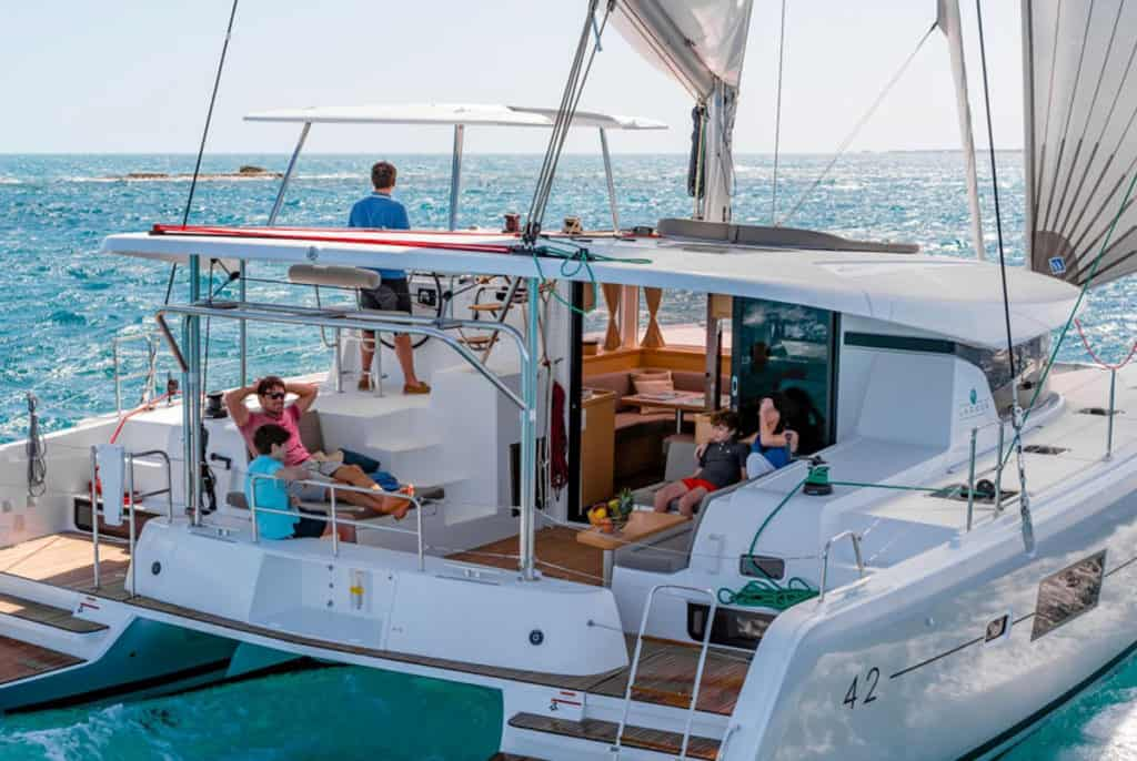 cyclades skippered sailing catamaran with family group relaxing