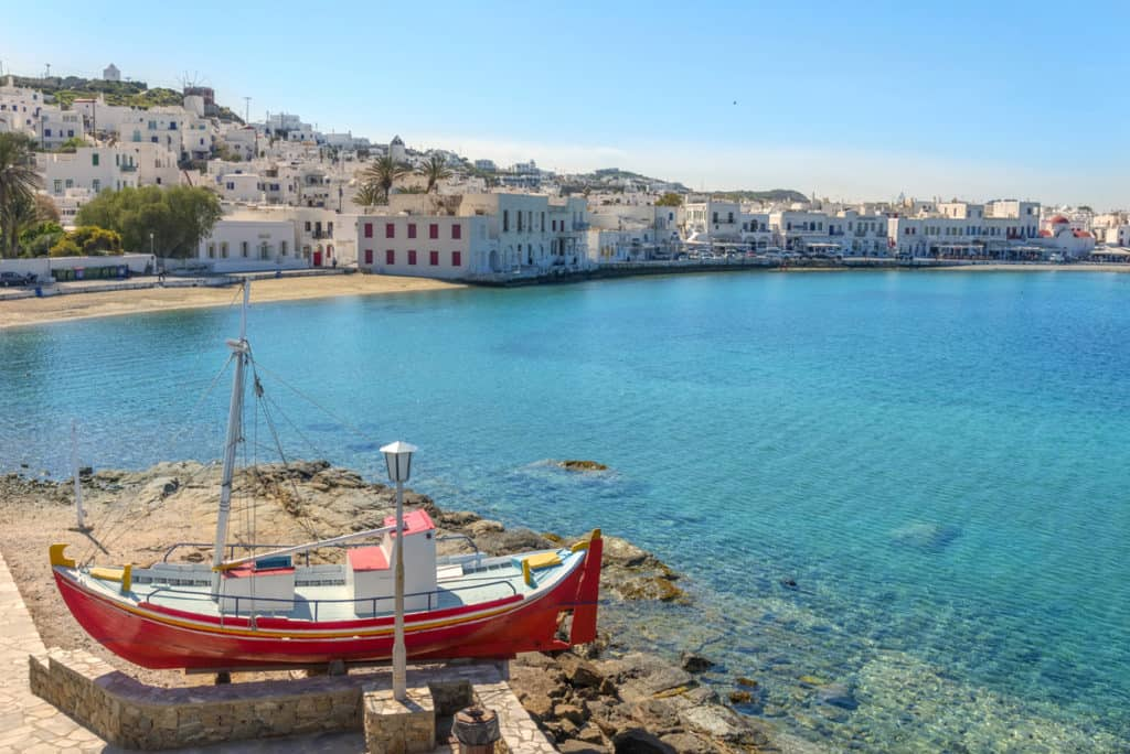 cyclades skippered sailing along the coast of a pretty greek island with a town