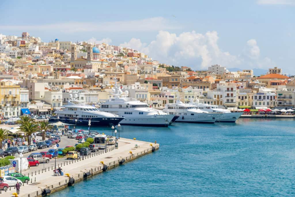 syros island with many luxury yachts moored at a marina