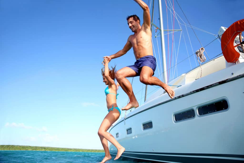 cyclades skippered sailing couple jump from a yacht into the blue sea