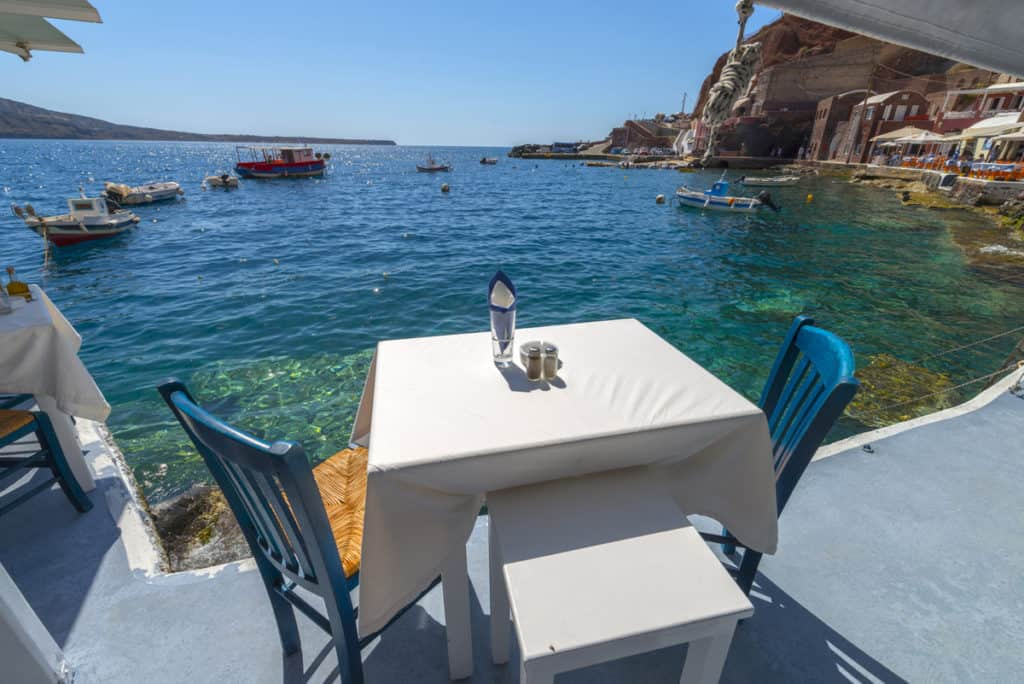 cyclades skippered sailing table beside the sea in a beauriful bay on a greek island