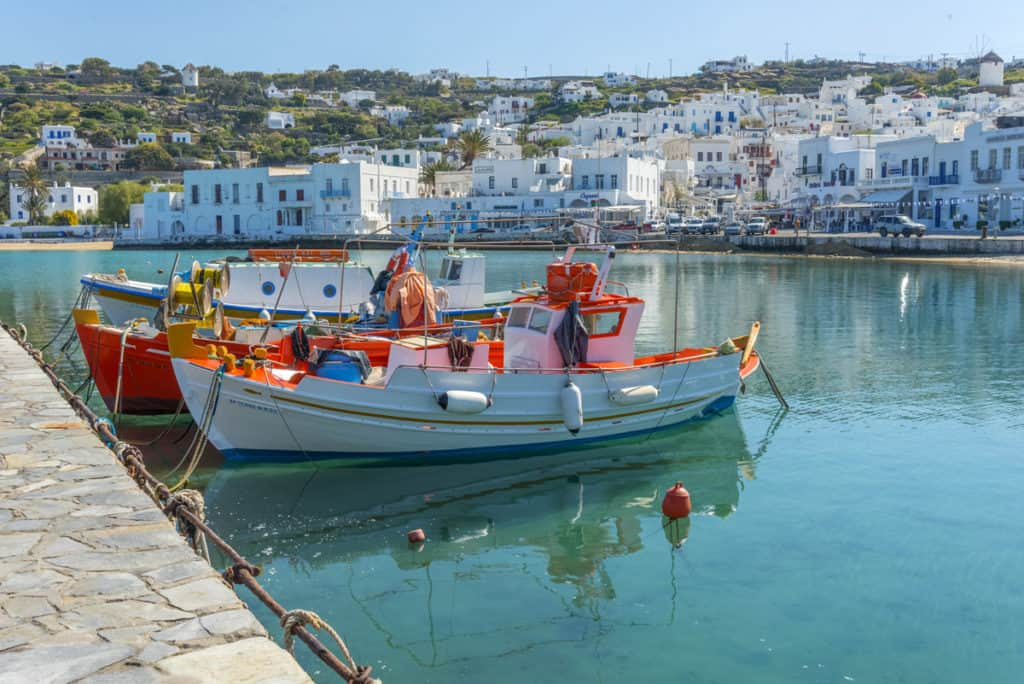 cyclades skippered sailing at a peaceful greek fishing port with pretty small colourful boats
