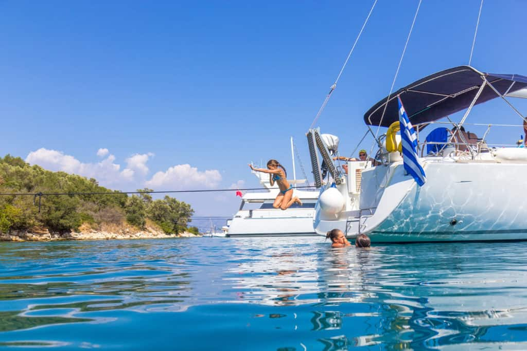 cyclades skippered sailing with a family group as children jump from a boat