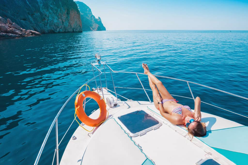 cyclades skippered sailing with woman in swimming costume relaxes on a yacht