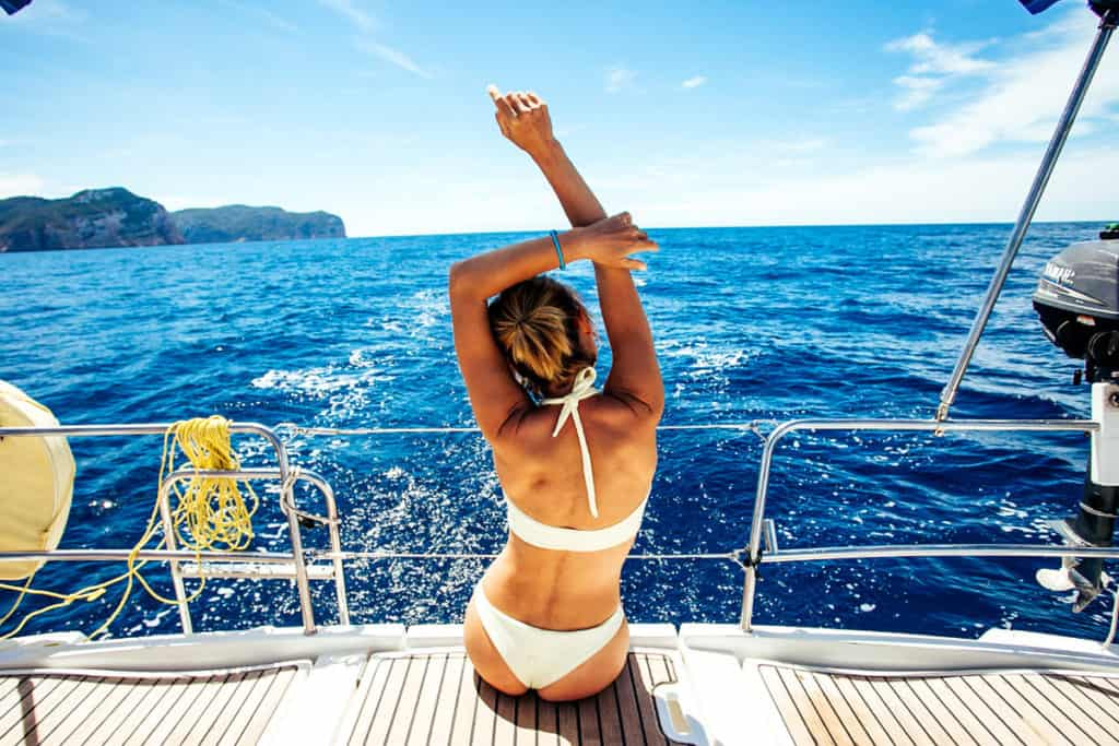 cyclades skippered sailing with girl in bathing suit sitting on a yacht